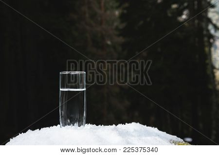 A transparent glass glass with drinking mountain water stands in the snow against a background of a forest in winter. The concept of drinking mountain drinking mineral water and the production of mineral environmentally friendly drinking water