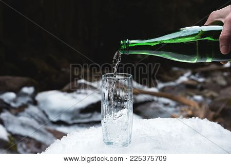 Mineral mineral water is poured from a glass green bottle into a clear glass beaker. A glass stands in the snow. Against the background of a winter forest and a rugged mountain stream with ice and rocks.