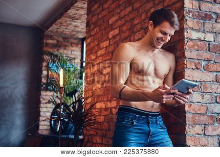 A sexy tattoed shirtless man with touchpad leans against the brick wall. Smiling and looking away.