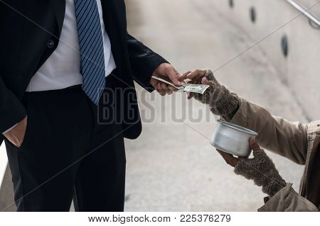 Business Man Giving One Dollar Bill Money To Beggar O Homeless Guy At City Walk In Urban Town. Pover