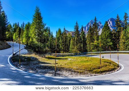 Dolomite Alps. Beautiful sunny day. The road passes in the coniferous forests at the foot of limestone and dolomite rocks. The concept of active, extreme and car tourism