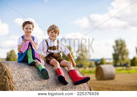 Two little kid boy and girl in traditional Bavarian costumes in wheat field. German children sitting on hay bale during Oktoberfest. Siblings play at hay bales during summer harvest time in Germany