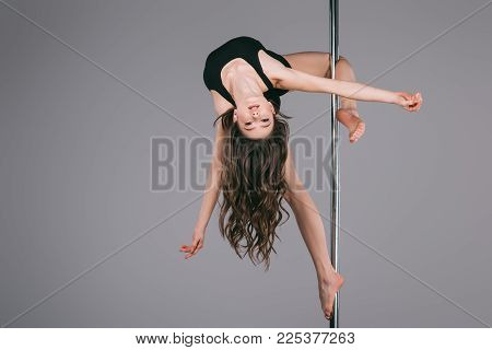 Upside Down Of Beautiful Female Dancer In Sportswear Exercising With Pole And Looking At Camera On G