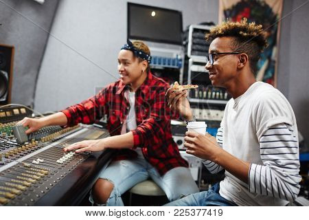 Young sound operator with drink and slice of pizza having lunch while his colleague working by soundboard