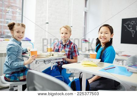 Three cute schoolkids sitting in classroom at break and having lunch and drinks between lessons