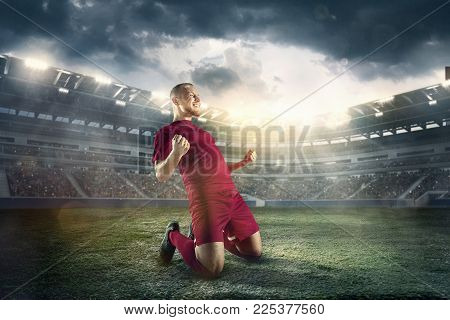 Happiness football player after goal on the field of stadium with lights. The professional football, soccer player and human emotions concept