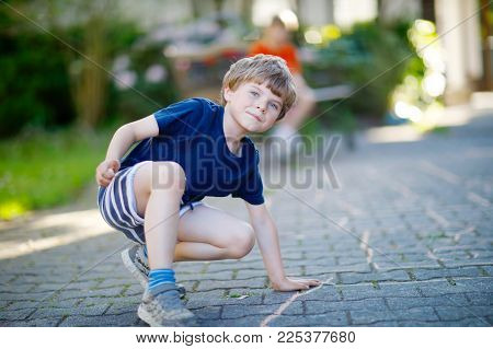 Little blond funny kid boy playing hopscotch on playground outdoors. Happy child having fun with outdoor activities in summer on sunny day.