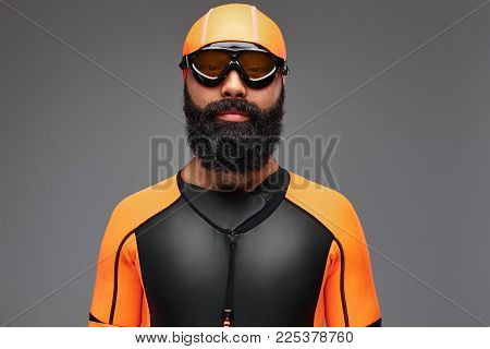 Portrait of a bearded male in orange neoprene diving suit and dive mask isolated on grey background.