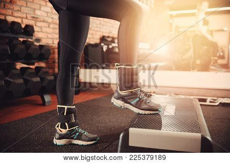 Aerobics. Close-up of athletic shoes, girl performs exercise step on podium with weighting. Concept of weight loss
