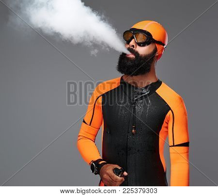 Portrait of a bearded male in orange neoprene diving suit and dive mask smoking an electronic pipe. Isolated on grey background.
