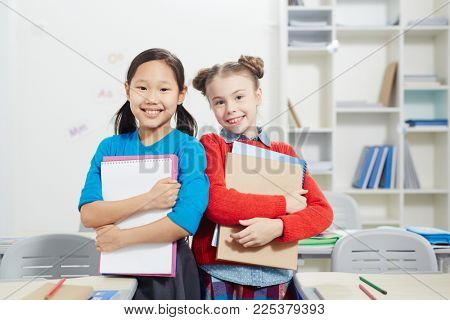 Two intercultural schoolgirls with books standing in aisle between rows of desks in classroom
