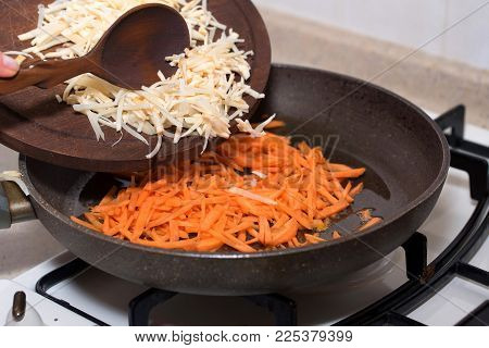 Close up woman's hands adding chopped parsnip to carrot on frying pan for cooking soup