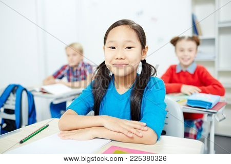 Little diligent girl sitting by her desk with two classmates on background