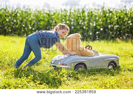 Little preschool kid girl driving big vintage old toy car and having fun with playing with big plush toy bear, outdoors. Child enjoying warm summer day in nature landscape. Girl driving car.