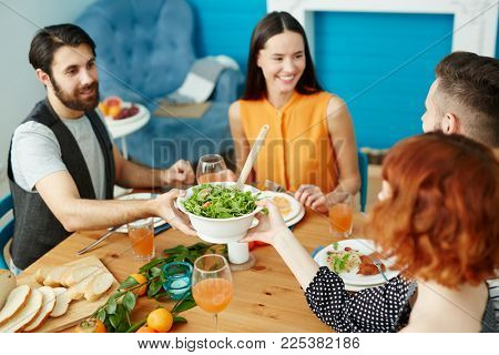 Young man passing over bowl with fresh vegetarian salad to one of girls by dinner