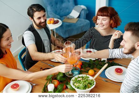 Two happy couples toasting with glasses of juice over served table with healthy food