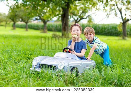 Two happy children playing with big old toy car in summer garden, outdoors. Boy driving car with little girl inside. Laughing and smiling kids. Family, childhood, lifestyle concept.