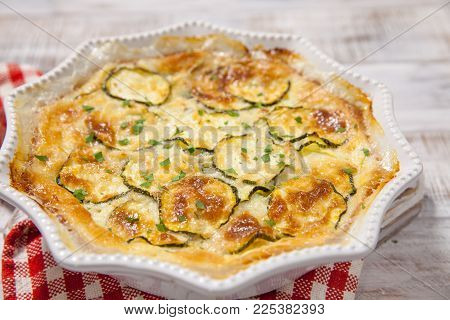 Low carb Green Zucchini casserole with cheese in baking dish