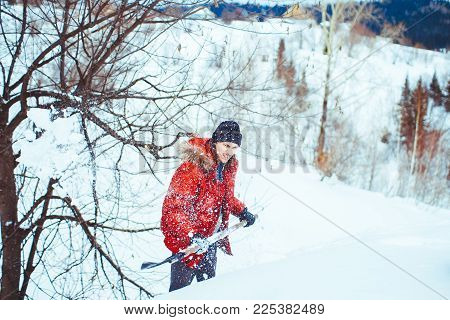 a young man shovelling snow on blue sky background