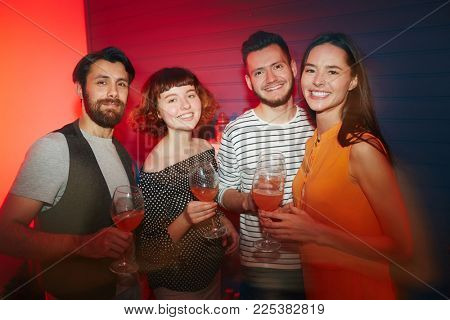 Four cheerful young people with glasses of refreshing juice looking at camera with smiles