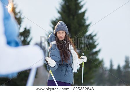 Scowling female looking at her boyfriend while talking to him during ski training outdoors