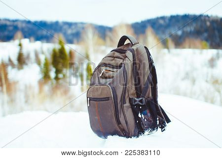 backpack on the background of snow-capped mountains and blue sky. Backpack in the snow. Active lifestyle. Hiking in the winter.