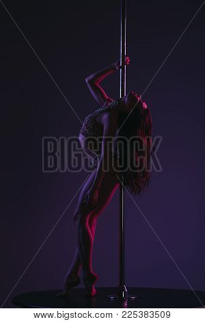 Side View Of Seductive Flexible Pole Dancer Posing With Pylon On Blue