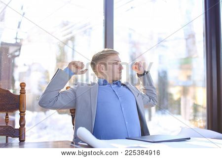 Construction Company Manager Sitting At Cafe, Resting With Drafting Project And Black Document Cases