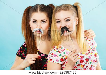 Two Happy Women Holding Fake Moustache On Stick Having Fun Wearing Tshirts With Flower Pattern. Phot
