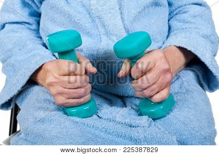 Close up picture of senior woman's hands holding blue dumbells, physiotherapy on isolated