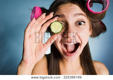 Happy Woman With Big Curlers On Head On Blue Background Holds A Cucumber Arm