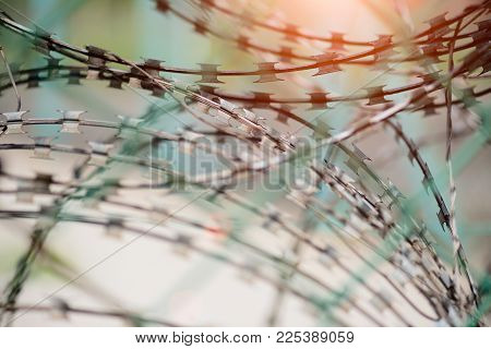 Closeup a security fence with barbed wire. Human Rights and social justice abstract concept.