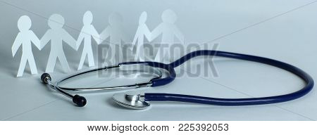stethoscope and paper men on the table.the concept of family medicine