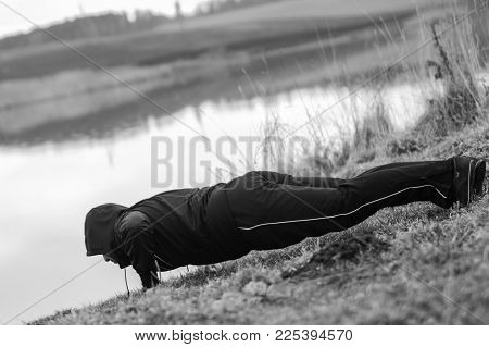 Charismatic sportsman is doing sports exercises by the lake. Push up. Dressed in a tracksuit, a little cold because of early spring time.