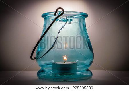 Studio Picture Of Light Blue Glass Lantern With Lit Candle