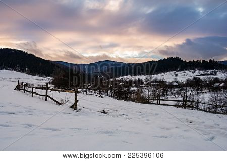Wooden Fence Along The Snowy Road. Beautiful Winter Landscape Of Mountainous Rural Area At Cloudy Su