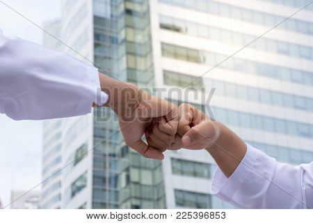 Close Up Of Two Hands Fist Bump To Show Work Together With City Background/success Concepts.