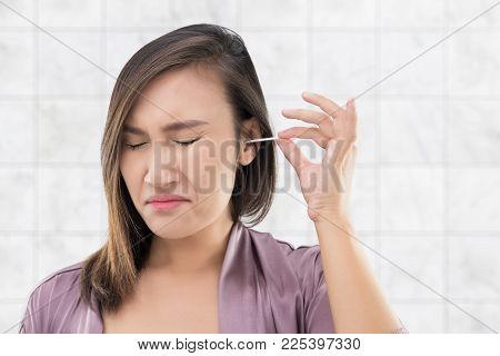 Asian women in robes cleans her ears with a cotton swab on bathroom, Hygiene and people concept