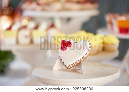 Glazed Gingerbread Heart Stands On The Wooden Stand In The Restaurant. It S Decorated With Glaze Red