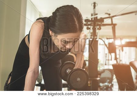 Slim Asian Woman Is Lifting Weight Dumbbell In Fitness Gym