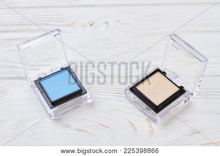 Set Of Mono Eyeshadows On Wooden Background. Two Plastic Containers Of Blue And Beige Mineral Eyesha