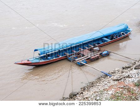 Long Tail Boat Is Floating Near The Local Pontoon On The Large River,northern Of Thailand.