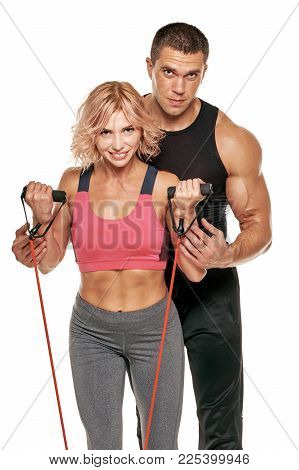 Portrait Of Two Smiling People Working Out With Elastic Expander