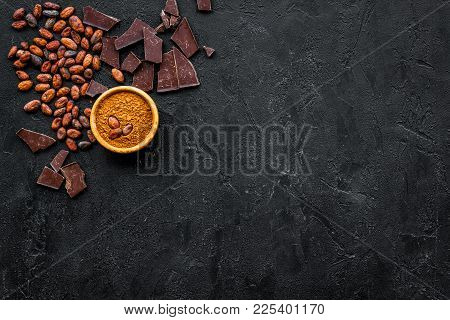 Chocolate And Cacao Concept. Cocoa Powder In Bowl Near Cocoa Beans And Broken Chocolate On Black Bac