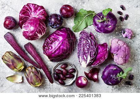 Raw Purple Vegetables Over Gray Concrete Background. Cabbage, Radicchio Salad, Olives, Kohlrabi, Car