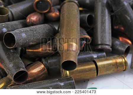 Heap Of Gun Bullets. Weapon Cartridge Case Sleeve Background Texture, 7.65, And 9mm. Weapon Cartridg