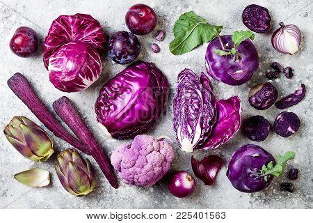 Raw Purple Vegetables Over Gray Concrete Background. Cabbage, Radicchio Salad, Kohlrabi, Carrot, Cau