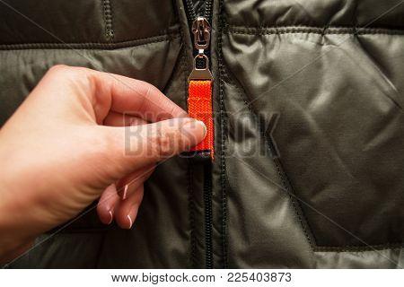 Hand Unbuttons An Orange Zipper On A Green Jacket