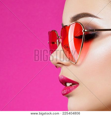 Closeup Portrait Of Young Beautiful Woman Red Wearing Heart Shaped Glasses. Smokey Eyes And Red Lips