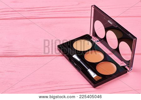 Beige Color Eyeshadows Palette. Bronze Eyeshadows On Pink Wooden Background. Color Lipstick Palette.